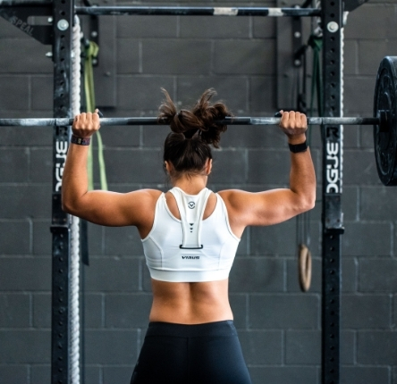 a woman lifts a weight above her head