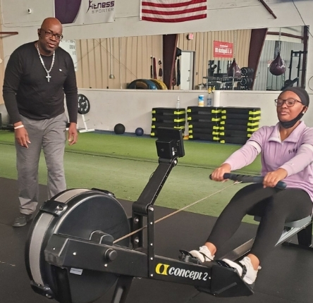 a woman rows on a rowing machine as dwayne adams coaches her during the workout