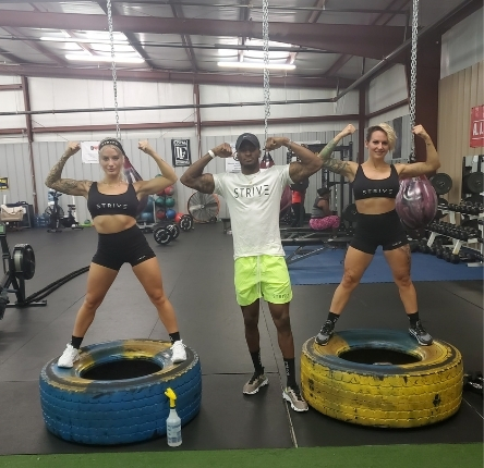 a breaking barriers rowing and fitness trainer flexes his muscles with two female clients