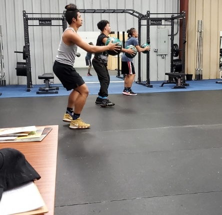 three young men workout using weighted balls