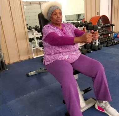 a senior citizen uses light weights during a training session