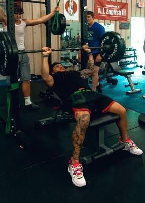 one man bench presses while another keeps watch