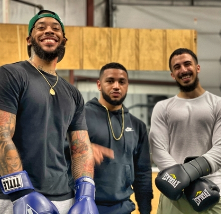 three men pose with boxing gloves on their hands