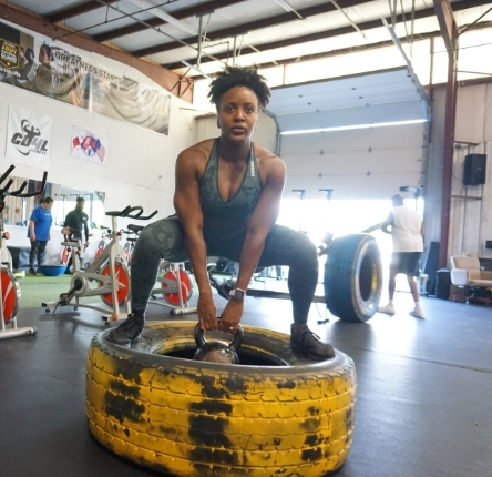 a woman holds a bell weight while squatting on a large tire