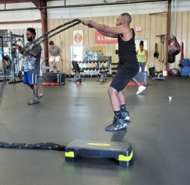 a muscular black man uses ropes during a workout