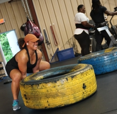 a fit black woman lifts a giant yellow tire during a workout