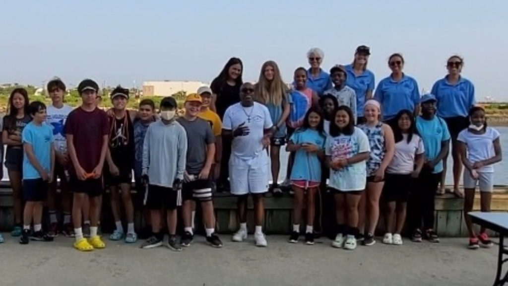 dwayne adams with the kids from the summer youth rowing program