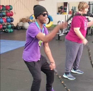a blind man uses ropes during a group workout