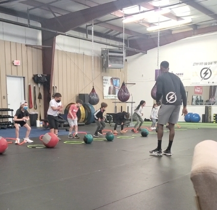 young kids work out using rings and heavy weight balls